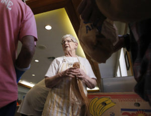 Muriel Dufendach hands plastic bags to people in need of food